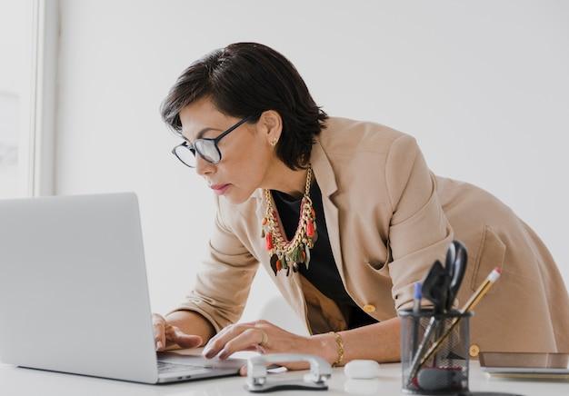 Oudere vrouw die aan laptop werkt