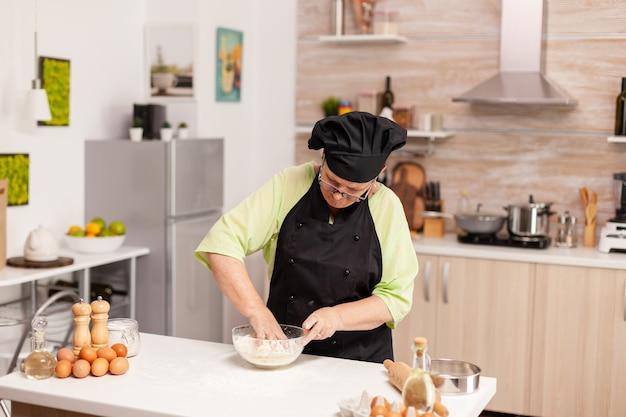Oudere vrouw die bonete draagt tijdens het bereiden van deeg voor pasta in de thuiskeuken volgens traditioneel recept