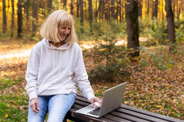 Oudere vrouw die buitenshuis laptop met behulp van