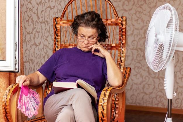 Oudere vrouw die de bijbel leest, zittend in een stoel bij een open raam en een elektrische ventilator in de hitte