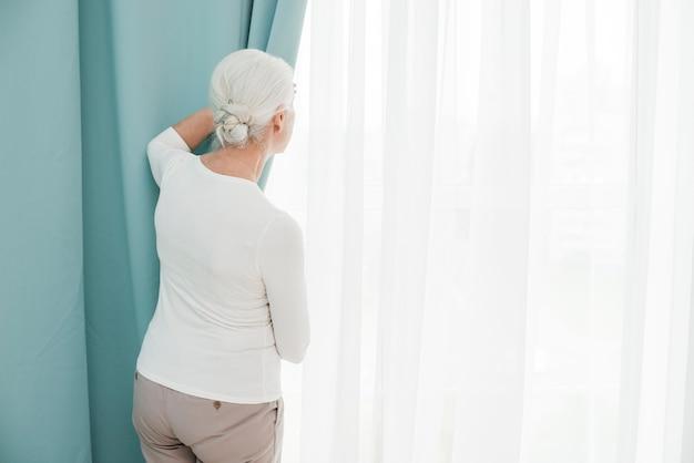 Oudere vrouw die door het venster kijkt