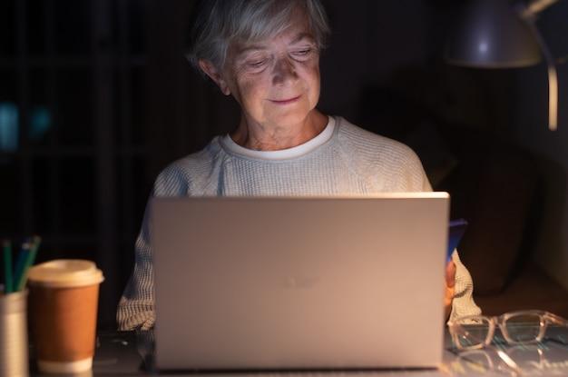 Oudere vrouw die door sociale media-inhoud bladert met behulp van een laptop op een bureau met een mobiele telefoon. oude gepensioneerde vrouw die 's nachts haar tijd doorbrengt door op laptop te werken