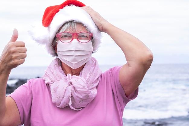 Oudere vrouw die een beschermend masker draagt vanwege de covid19 die op het strand staat met een kerstmuts