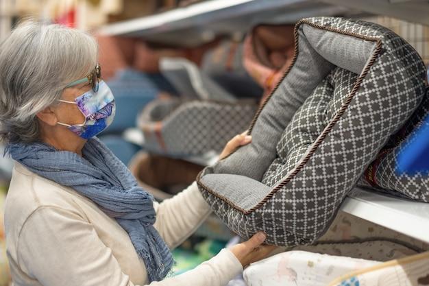 Oudere vrouw die een chirurgisch masker draagt vanwege het coronavirus doet aankopen op de dierenafdeling. ze kiest een zacht bed voor haar hond