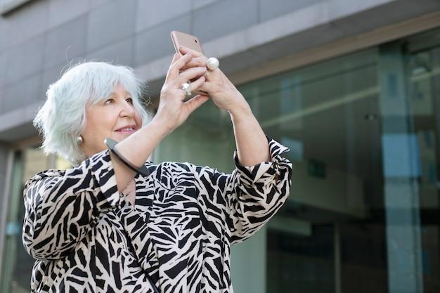 Oudere vrouw die een foto maakt in de stad