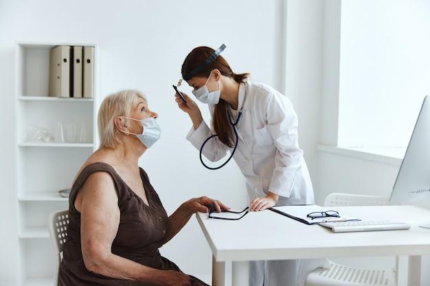 Oudere vrouw die een medisch masker draagt bij de doktersgezondheidszorg