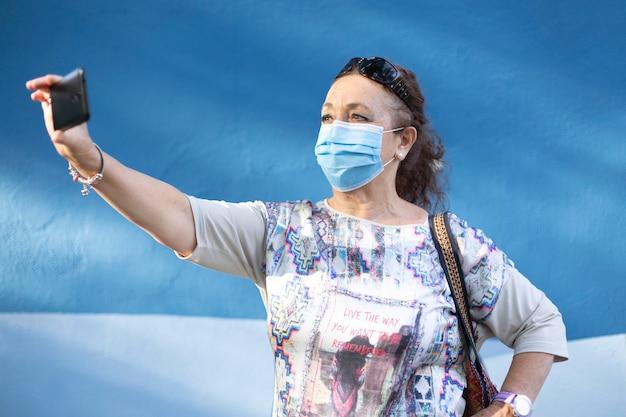 Oudere vrouw die een medisch masker draagt en een selfie neemt dichtbij een blauwe muur.