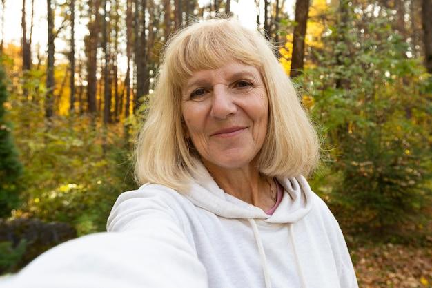 Oudere vrouw die een selfie buiten in de natuur neemt