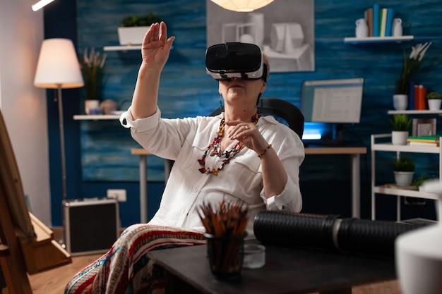 Oudere vrouw die een vr-bril gebruikt voor virtuele inspiratie om te tekenen