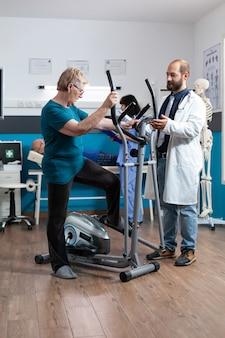 Oudere vrouw die elektrische fiets gebruikt voor lichaamsbeweging