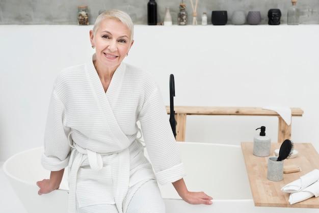 Oudere vrouw die en in badjas glimlacht stelt