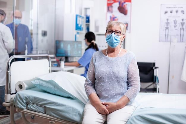 Oudere vrouw die gezichtsmasker draagt tegen covid terwijl ze wacht op dokter in ziekenhuiskast voor medische afspraak