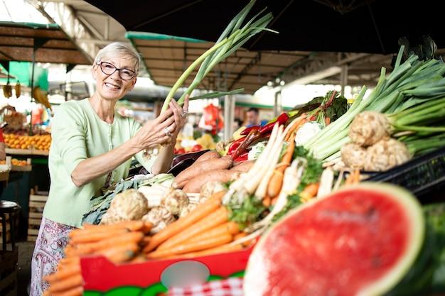Oudere vrouw die gezonde groenten kiest en koopt op de markt.