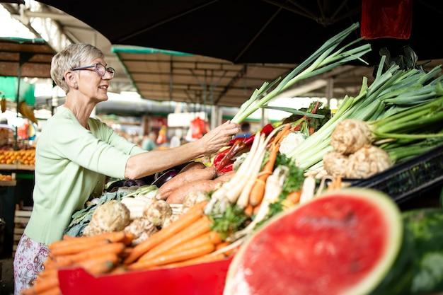 Oudere vrouw die gezonde groenten op de markt kiest en koopt.