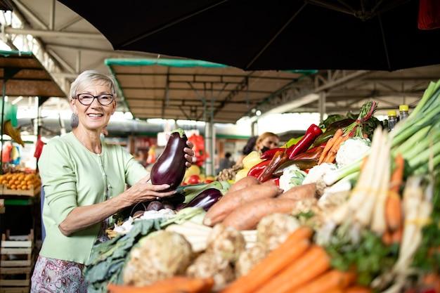 Oudere vrouw die groenten koopt op de markt.