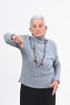 Oudere vrouw die haar duim en ernstig op witte achtergrond laag houdt