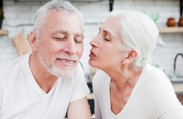Oudere vrouw die haar echtgenoot kust