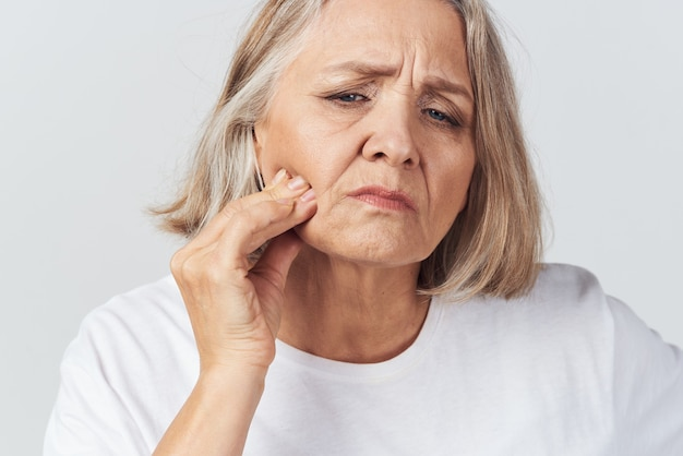 Oudere vrouw die haar hoofd vasthoudt migraine pijnbehandeling