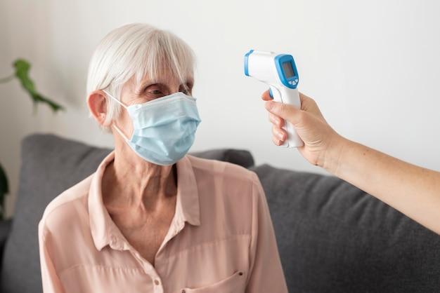 Oudere vrouw die haar temperatuur met thermometer heeft gecontroleerd
