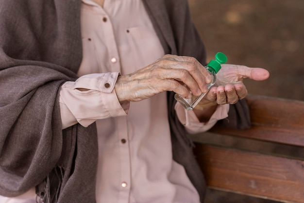 Oudere vrouw die handdesinfecterend middel gebruikt