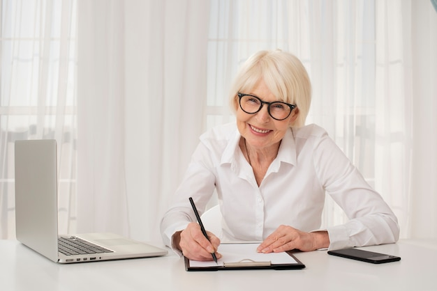 Oudere vrouw die in een klembord schrijft