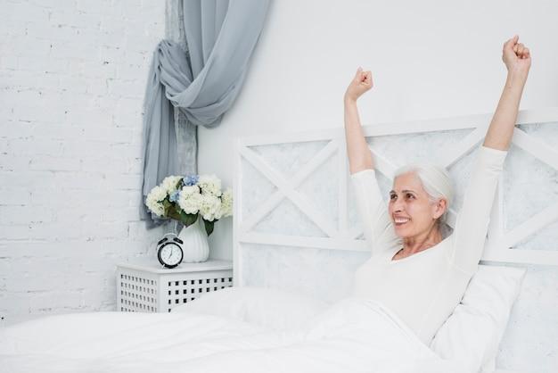 Oudere vrouw die in het bed ontwaakt