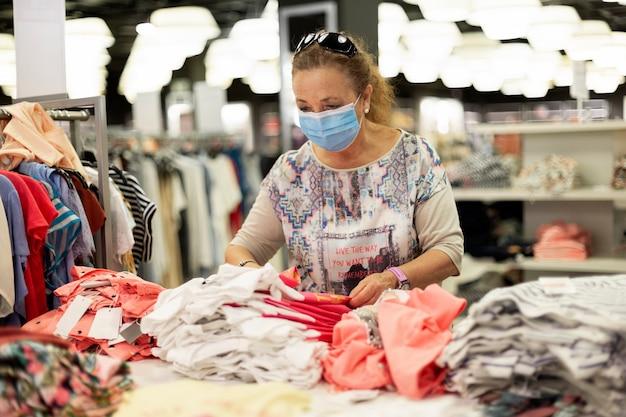 Oudere vrouw die kleren in een winkel bekijkt.