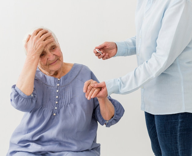 Oudere vrouw die koorts heeft terwijl thuis