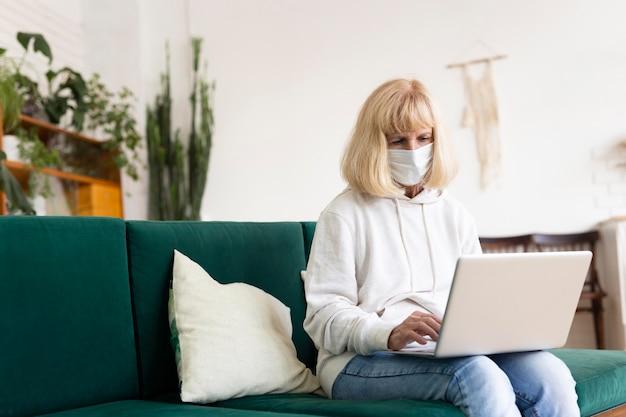 Oudere vrouw die laptop thuis met medisch masker met behulp van