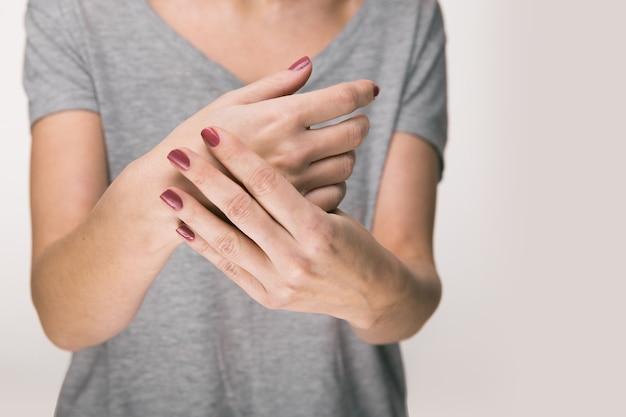Oudere vrouw die lijdt aan pijn, zwakte en tintelingen in de pols. oorzaken van pijn zijn onder meer artrose, reumatoïde artritis, jicht of verstuiking van de pols. zorgconcept