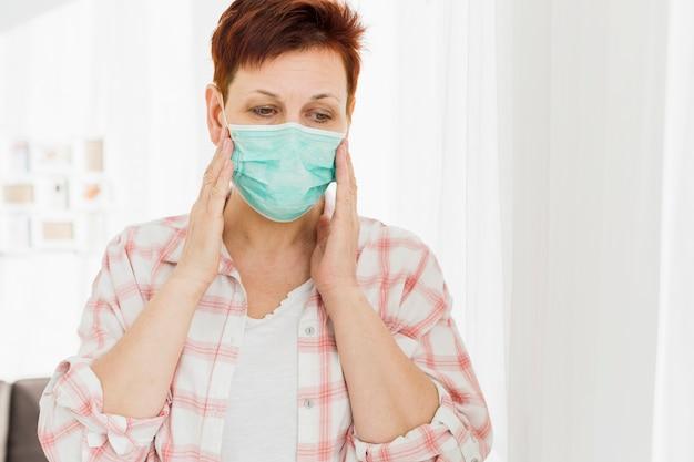 Oudere vrouw die medisch masker thuis draagt