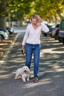 Oudere vrouw die met een hond buiten loopt.