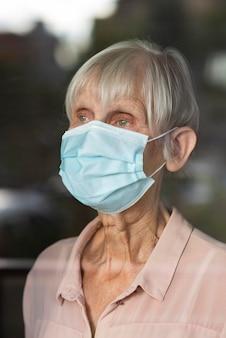 Oudere vrouw die met medisch masker door glasvenster kijkt