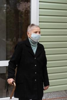 Oudere vrouw die met medisch masker een stok draagt