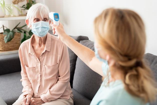 Oudere vrouw die met medisch masker haar temperatuur door verpleegster krijgt gecontroleerd