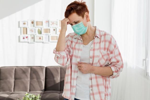Oudere vrouw die met medisch masker ziek voelt