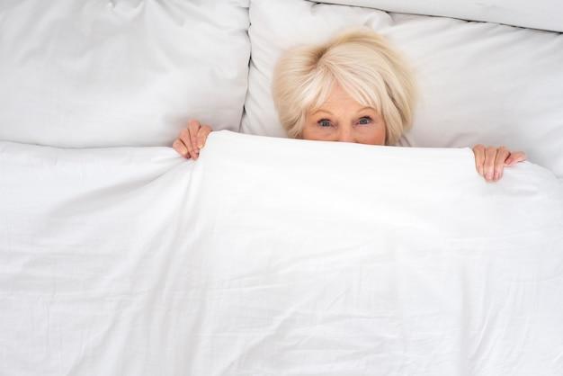 Oudere vrouw die onder deken legt