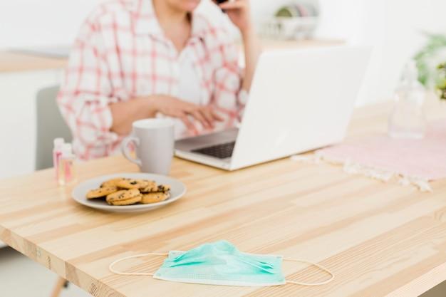 Oudere vrouw die op de telefoon spreekt en aan laptop werkt
