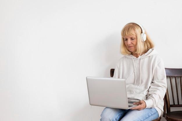 Oudere vrouw die op laptop thuis werkt en hoofdtelefoons draagt