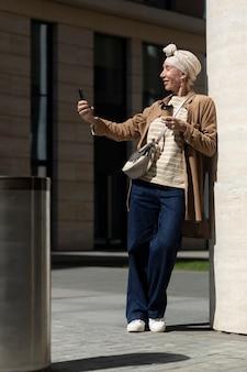 Oudere vrouw die selfie maakt met smartphone buiten in de stad