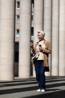 Oudere vrouw die smartphone buiten in de stad gebruikt