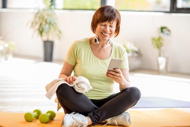 Oudere vrouw die smartphone gebruikt na sporttraining die binnenshuis of in de sportschool zit