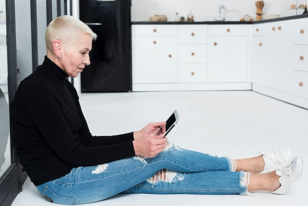 Oudere vrouw die tablet in de keuken bekijkt