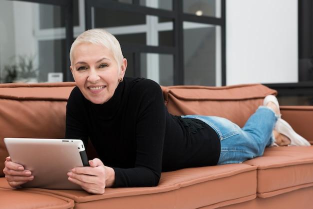 Oudere vrouw die terwijl het zitten op bank en het houden van tablet glimlacht
