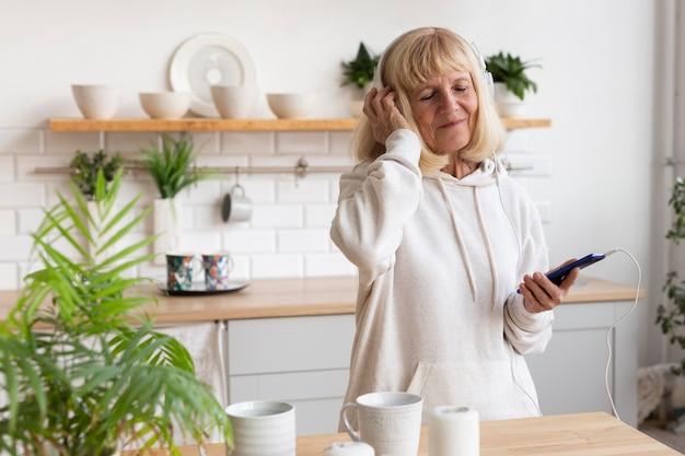 Oudere vrouw die thuis aan muziek op hoofdtelefoons luistert