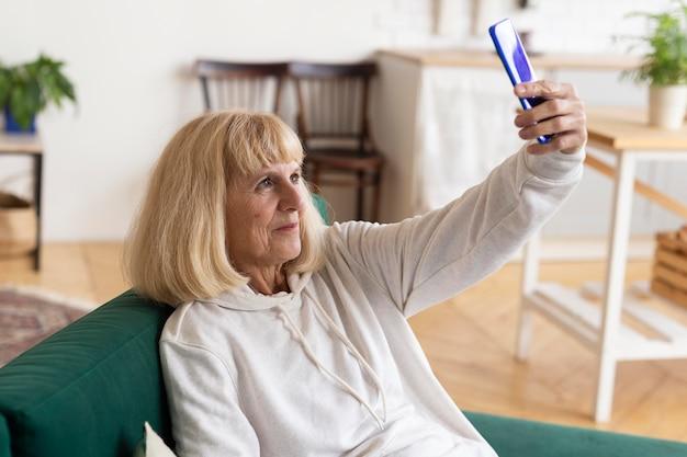 Oudere vrouw die thuis een selfie neemt