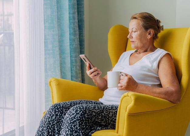 Oudere vrouw die thuis smartphone gebruikt tijdens de pandemie terwijl ze koffie drinkt