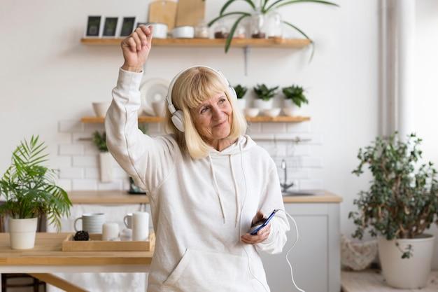 Oudere vrouw die thuis van muziek op hoofdtelefoons geniet