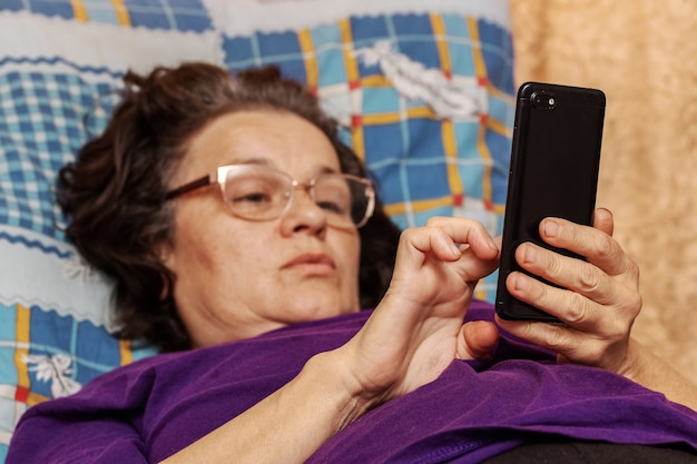 Oudere vrouw die tijdens ziekte in bed ligt met een telefoon in haar handen
