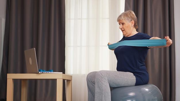 Oudere vrouw die traint tijdens online training met behulp van weerstandsband. online training leertechnologie oude vrouw tillen training gezonde levensstijl sport fitness workout thuis met gewichten dumbb